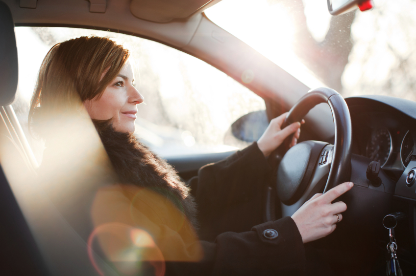 Woman driving her car and smiling