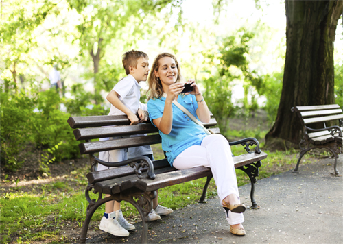 Mother and son in park with mobile device