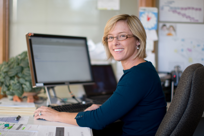 Woman Smiling at Office Computer