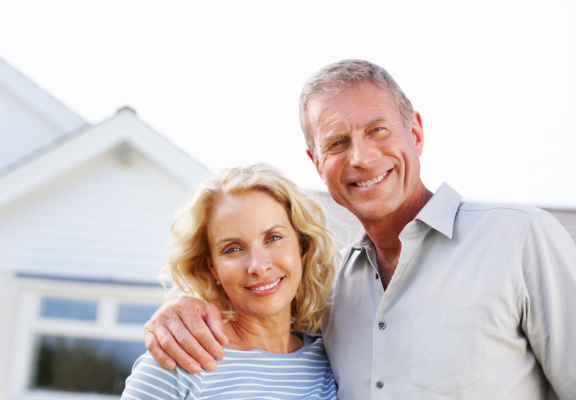 Smiling Older Couple Standing in front of a house
